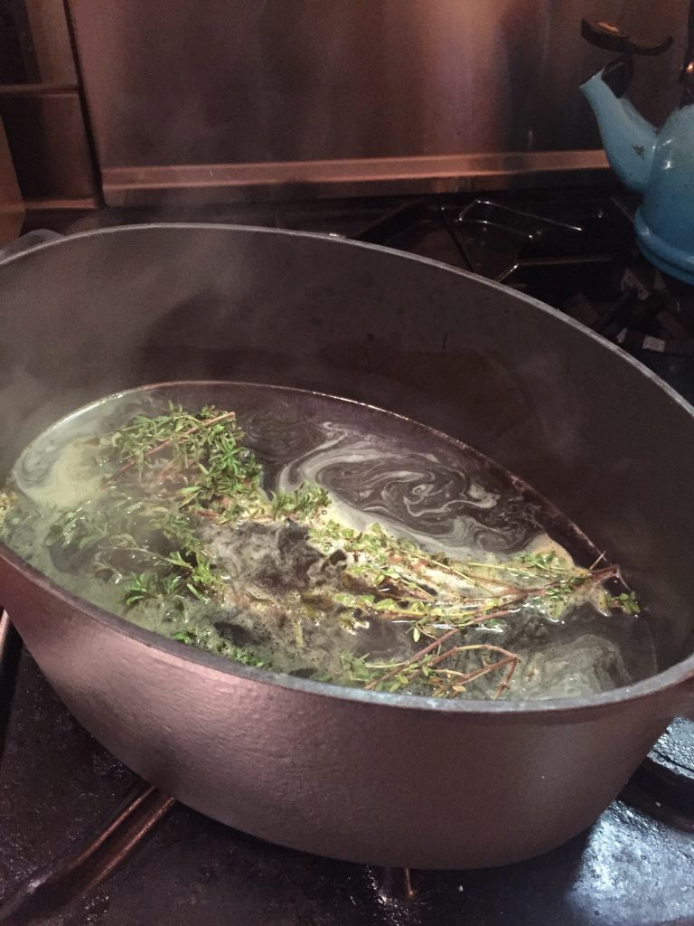 pot with wine and broth and herbs